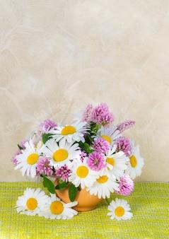 明るい背景の花瓶にクローバーとカモミールの花束。庭と野の花の夏の花束。ヒナギクのある静物。