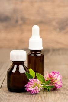 Цветы клевера и эфирное масло в коричневых стеклянных бутылках на деревянном деревенском столе