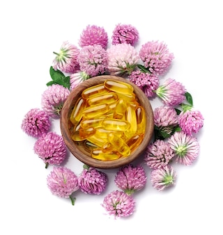 Изолированные цветки клевера и витамин.