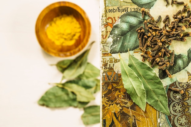 Cloves and bay leaves near blurred turmeric