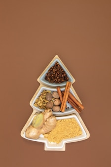Cloves, cinnamon, nutmeg, cardamom and ginger for making ginger cookies in a box in the shape of a christmas tree with copy space. concept of festive christmas baking. top view, flat lay.