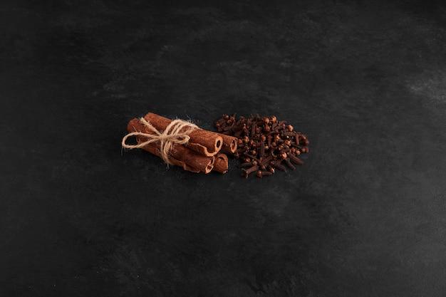 Cloves and cinnamon sticks on black surface