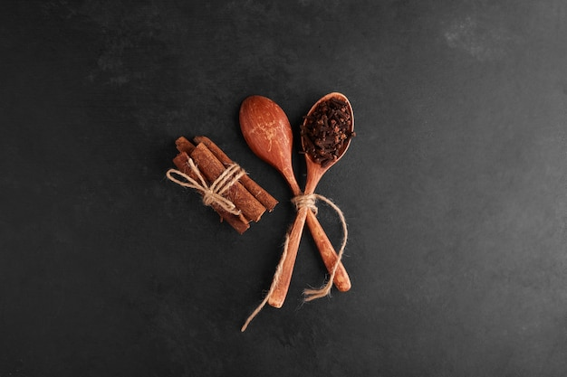 Cloves and cinnamons in a wooden spoon.