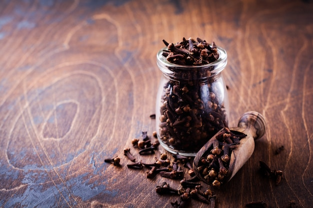 Cloves. dry seasoning for cooking and drinks on a simple old wooden background. selective focus