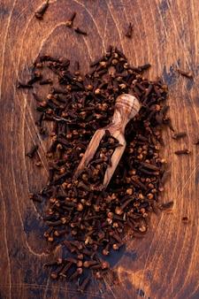 クローブ。シンプルな古い木製の背景に料理や飲み物のためのドライ調味料。セレクティブフォーカス。