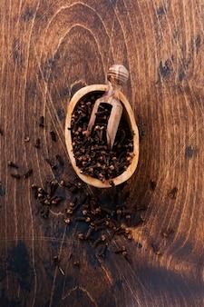 Гвоздика. сухая приправа для приготовления пищи и напитков на простой старый деревянный фон. выборочный фокус