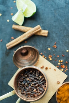 Cloves near cinnamon and lime