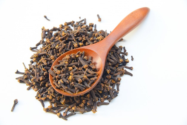 Cloves (spice) and wooden spoon on white background