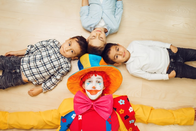 Clown and children pull hands into the camera