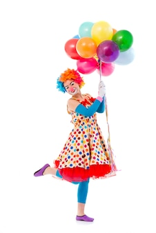 Clown in colorful wig holding balloons, standing on one leg.