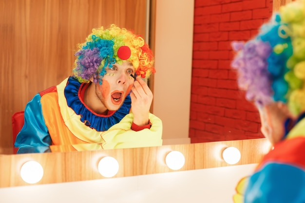 Clown does a make-up in front of the mirror.