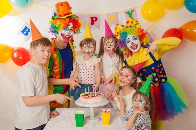 子供の誕生日パーティーでピエロの女の子とピエロの少年。美しいケーキとお祝いテーブル