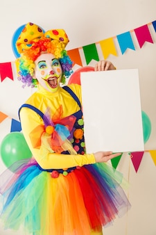 Clown girl on a holiday holding a white plate for inscriptions