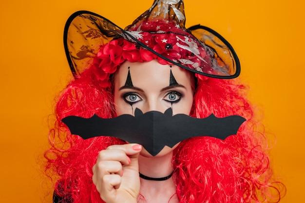 Девушка-клоун в костюме хэллоуина закрывает лицо бумажной летучей мышью, изолированной на оранжевом
