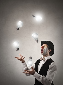 Clown juggling with light bulbs