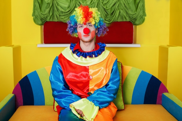 Clown sitting on colorful sofa.