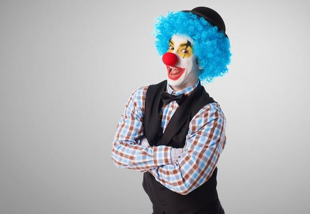 Клоун со скрещенными руками делает смешные лица