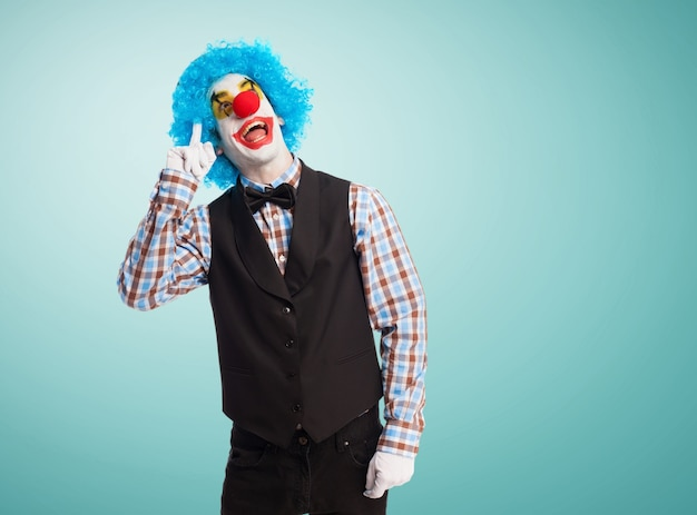 Clown with finger on forehead and smiling