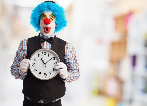 Clown with funny face holding a clock