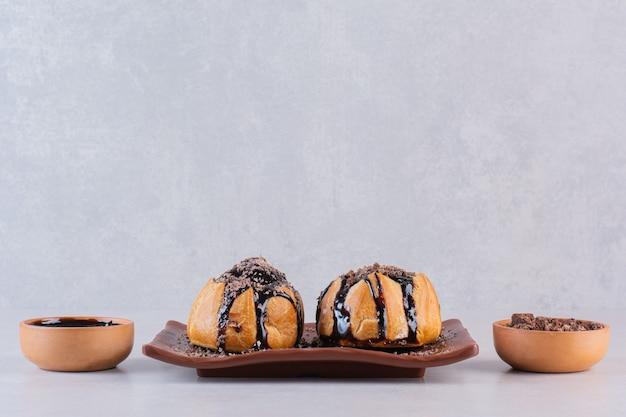 灰色の上の茶色のプレート上のチョコレートクッキーの写真をclsoeup