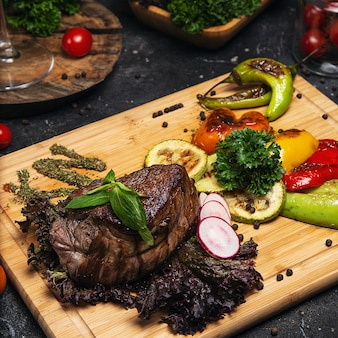 Club beef steak with pepper sauce and grilled vegetables on cutting board