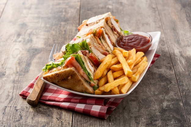 クラブサンドイッチとフライドポテトとケチャップソースの木製テーブル
