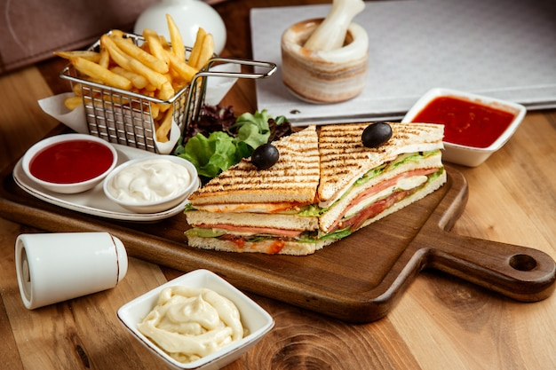 Club sandwich chicken tomato lettuce ketchup mayo and french fries on board