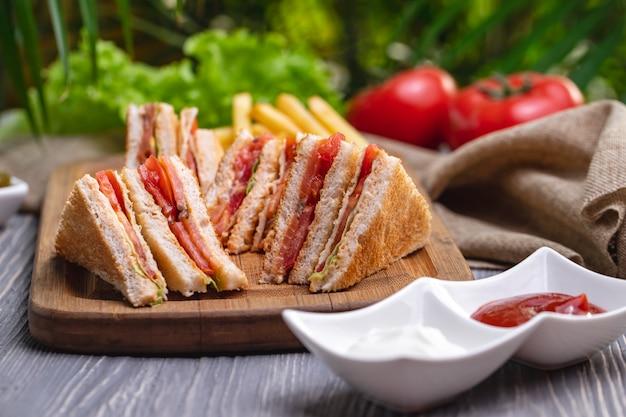 Клубный сэндвич с ветчиной курица томатный салат кетчуп майонез вид сбоку