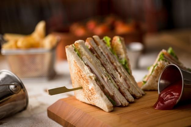 나무 접시에 클럽 샌드위치