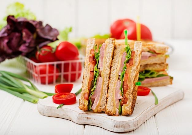 Клубный сэндвич - панини с ветчиной, сыром, помидорами и зеленью. вид сверху