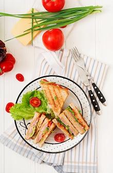 Club sandwich - panini con prosciutto, formaggio, pomodoro ed erbe. vista dall'alto