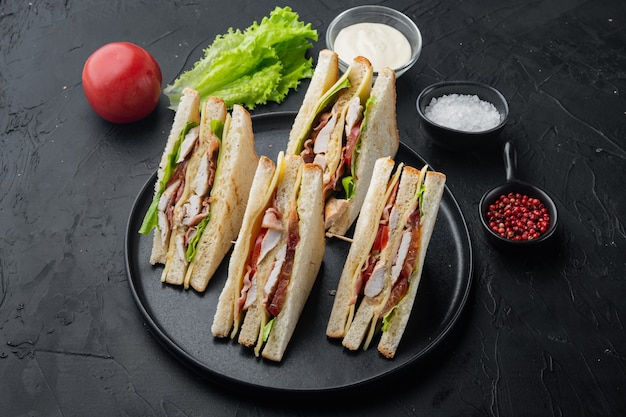Club sandwich panini with ham, fresh tomato, cheese, on black background