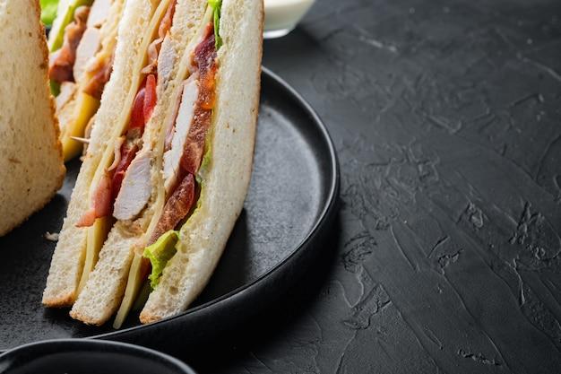햄, 신선한 토마토, 치즈, 블랙 테이블에 클럽 샌드위치 파니니