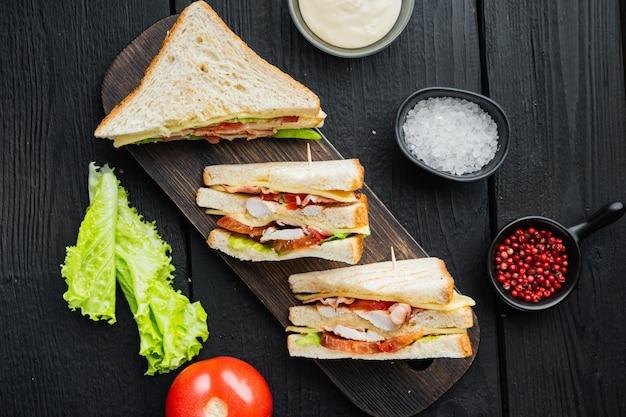 クラブサンドイッチパニーニ、ハム、フレッシュトマト、チーズ、黒い木製のテーブル、上面図