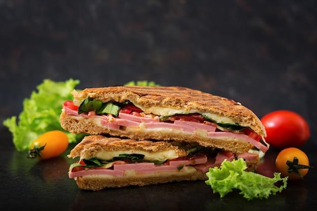 Клубный сэндвич панини с ветчиной, помидорами, сыром и листьями салата