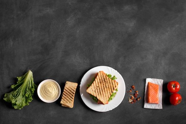 Club sandwich prepared with fish on the chalkboard
