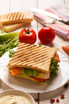 Club sandwich prepared with fish on the white wooden board