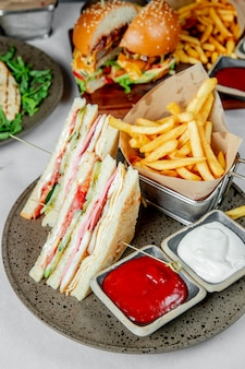 Club sandwich served with french fries ketchup and mayonnaise