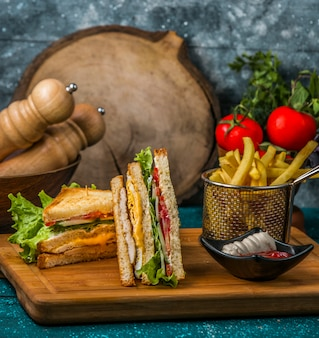 Club sandwich served with fries, mayonnaise and ketchup on wood serving board