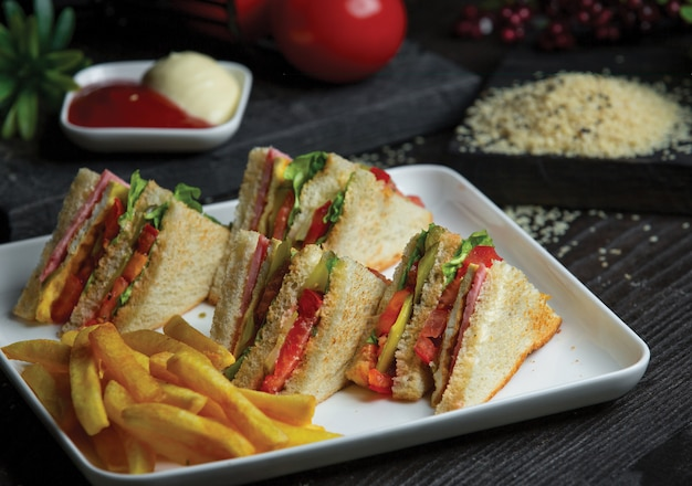 Club sandwich in white tray with roasted potatoes.