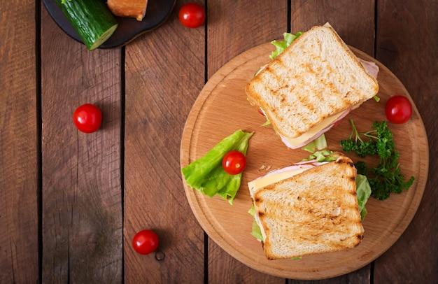 Клубный бутерброд с сыром, огурцом, помидорами, ветчиной и яйцом.