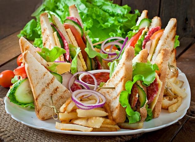 Клубный бутерброд с сыром, огурцом, помидорами, копченым мясом и салями. подается с картофелем фри.