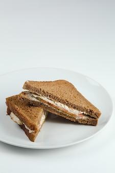 격리 된 하얀 접시에 호밀 빵에 닭고기와 토마토를 곁들인 클럽 샌드위치. 클럽 샌드위치.