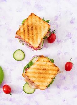 Клубный сэндвич с куриной грудкой, беконом, помидорами, огурцами и зеленью. вид сверху