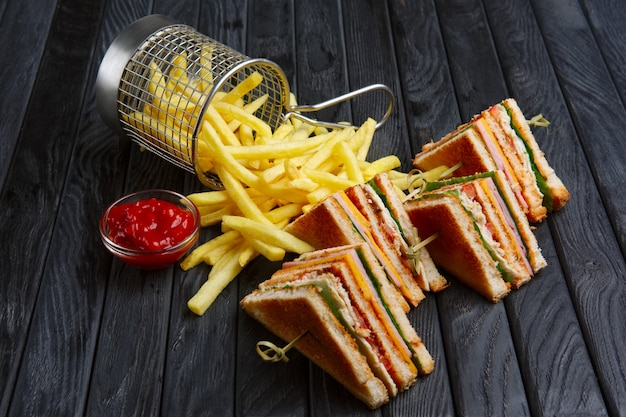 Club-sandwich with french fries in metal basket