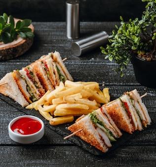 Club sandwich con patatine fritte sul tavolo