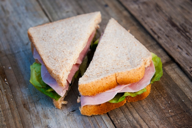 Club sandwich with ham and vegetables. rustic wooden .