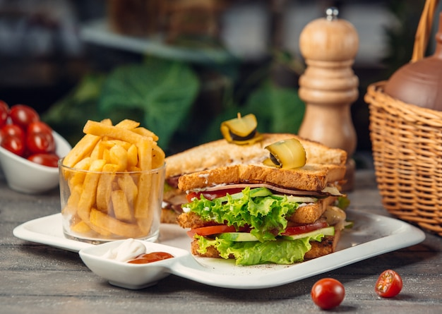 Club sandwich with lettuce, tomato, cucumber, turkey breast, fries