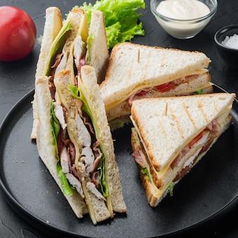 Клубный сэндвич с мясом, сыром, помидорами, ветчиной, на черном фоне