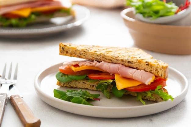 Клубный бутерброд с мясом, ветчиной, листьями салата, сыром. бутерброды поджаренного хлеба. легкая закуска или обед.